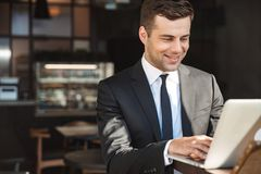 Handsome young businessman in formal clothes indoors in cafe using laptop computer royalty free stock photos