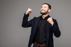 Handsome young businessman gesturing and smiling. While standing against grey background Stock Photography