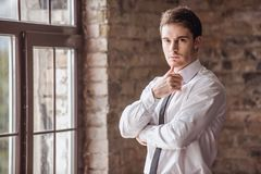 Handsome young businessman. Handsome pensive young businessman in suit is looking at camera while standing near the window royalty free stock photo