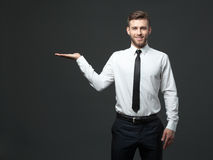 Handsome young businessman holding his arm up presenting copyspa Stock Photo