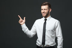 Handsome young businessman holding his arm up presenting copyspa Stock Photos