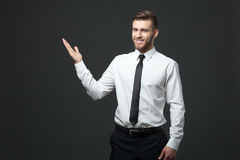 Handsome young businessman holding his arm up presenting copyspa Stock Images