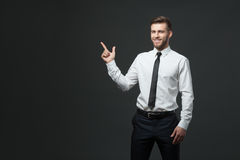 Handsome young businessman holding his arm up presenting copyspa Royalty Free Stock Image
