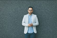 Young businessman with mobile phone by the grey wall. Handsome young businessman with mobile phone by the grey wall Royalty Free Stock Images
