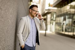 Young businessman with mobile phone by the grey wall. Handsome young businessman with mobile phone by the grey wall Stock Image