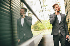 Handsome young businessman with mobile phone. By the office building Stock Photos