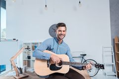 handsome young businessman playing guitar and smiling at camera royalty free stock photo