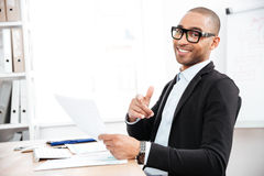 Handsome young businessman pointing finger at camera and holding papers Stock Image