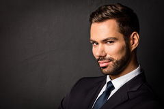 Handsome young businessman portrait on black background. Smart boss, manager Royalty Free Stock Photos