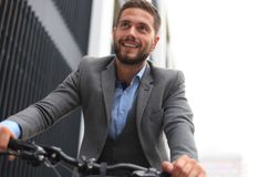 Handsome young businessman riding bicycle outdoors in the city. stock photos
