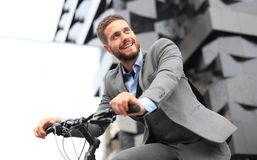 Handsome young businessman riding bicycle outdoors in the city. stock image