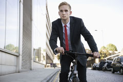 Handsome young businessman riding bicycle on street Royalty Free Stock Images