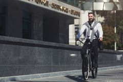 Handsome young businessman riding on his bicycle. Active millennial businessman riding bicycle to work, free space stock photography