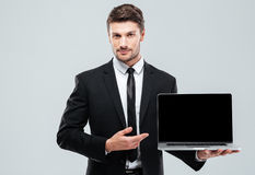 Handsome young businessman showing blank screen laptop Royalty Free Stock Image