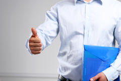 Handsome young businessman showing ok standing with folder Royalty Free Stock Photos