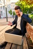 Young businessman siting on a bench with his laptop and talking royalty free stock images