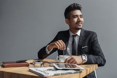 Handsome young businessman sitting in cafe and drinking coffee. stock photo