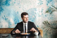Handsome young businessman sitting in cafe have a breakfast or dinner eat stock photo