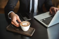 Handsome young businessman sitting in cafe using laptop computer drinking coffee royalty free stock image