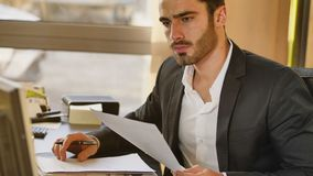 Handsome young businessman sitting at desk in office Stock Image