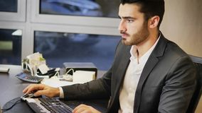 Handsome young businessman sitting at desk in office Royalty Free Stock Images