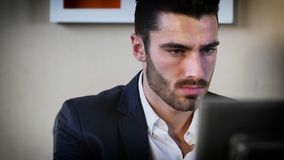 Handsome young businessman sitting at desk in office Royalty Free Stock Photos