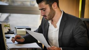 Handsome young businessman sitting at desk in office Royalty Free Stock Image