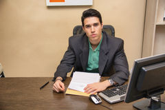 Handsome young businessman sitting at desk in Stock Photography