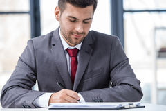 Handsome young businessman sitting at desk and writing in papers Stock Photos