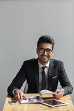 Handsome young businessman smiling and looking at camera in cafe while sitting against grey background. Royalty Free Stock Photography