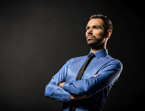 Handsome young businessman standing confident on black. Background. Smart boss, manager portrait with crossed arms Royalty Free Stock Photography