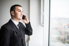 Handsome young businessman standing next to the large windows of his top floor office Royalty Free Stock Photos