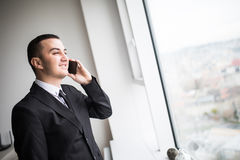 Handsome young businessman standing next to the large windows of his top floor office Stock Photos