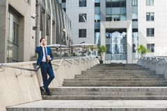handsome young businessman in stylish suit with coffee to go talking by phone on stairs royalty free stock image
