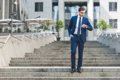 Handsome young businessman in stylish suit standing on stairs near business building and looking. At watch Stock Image