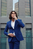 Handsome young businessman in stylish suit went to the terrace of his office to rest and have a cigarette Stock Image