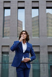 Handsome young businessman in stylish suit went to the terrace of his office to rest and have a cigarette Royalty Free Stock Photo