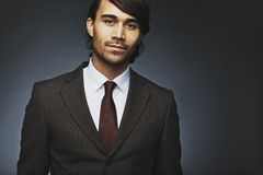 Handsome young businessman in suit. Portrait of handsome young businessman in suit looking at camera. Asian male fashion model in office attire against black Royalty Free Stock Images