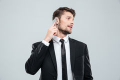 Handsome young businessman talking on mobile phone and looking back Royalty Free Stock Photography