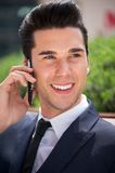 Handsome young businessman talking on phone outdoors Stock Photo