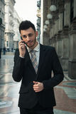Handsome young businessman talking on phone Stock Images
