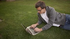 Handsome businessman typing on his laptop lying on a lawn, top view. Handsome young businessman typing at his laptop keyboard lying on the lawn. Locked down real stock video footage