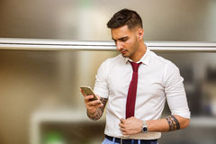 Handsome young businessman using cell phone. Handsome young businessman in his office typing and using cell phone, looking down, serious Royalty Free Stock Photography