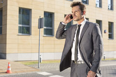 Handsome young businessman using cell phone outdoors Stock Images