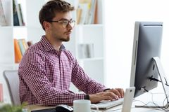 Handsome young businessman using his laptop in the office. Stock Image