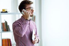 Handsome young businessman using his mobile phone in the office. Stock Image
