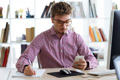 Handsome young businessman using his mobile phone in the office. Portrait of handsome young businessman using his mobile phone in the office Royalty Free Stock Photos