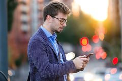 Handsome young businessman using his mobile phone in the street. Stock Image