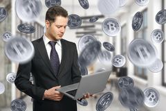 E-business and e-commerce concept. Handsome young businessman using laptop on abstract blurry office interior background with silver bitcoin rain. E-business and Royalty Free Stock Photography