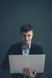 Handsome young businessman is using a laptop, looking at camera and smiling, on black background Stock Photo